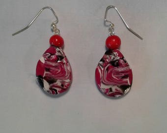 """Earrings in Mokume gane, oval shaped, colors of red, black, white, with black glass top beads. Resin finish, 2"""" long."""