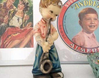 Little boy with saxophone plaster statue. Vintage