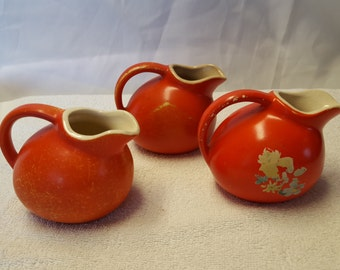 Ceramic pitchers, three small red, one with a decal