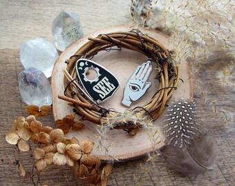 Set of 2 cloisonné / hard enamel lapel pins: See (Ouija pointer) and Providence (Hamsa hand).