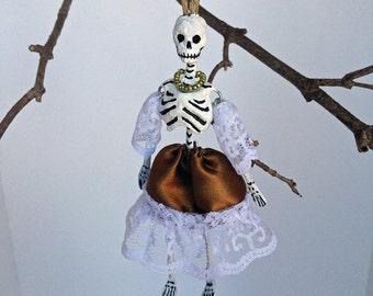 Paper mache Halloween ornament. Skeleton girl in brown dress.