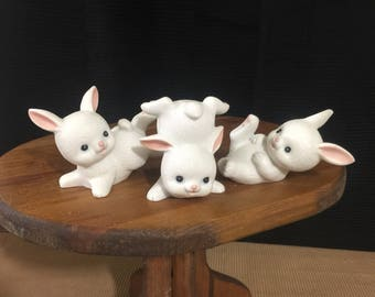 Three ceramic playful, pink and white blue eyed bunnies with pots of energy.