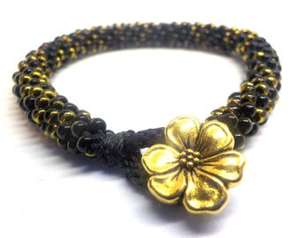 Black and gold beaded bracelet woven on a Kumihimo braid