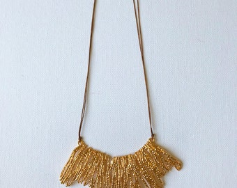 Long brown cord necklace with a large gold pendant