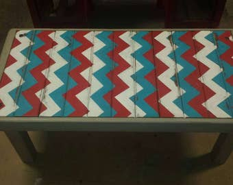 Hand painted coffee table with chevron patterns in an antique style.