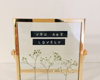 Framed pressed flowers with 'lovely' quote