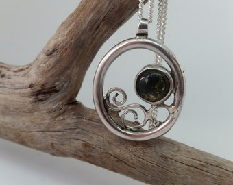 Circle swirl silver pendant with green amber stone.
