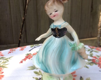 Vintage girl figurine in blue dress. Kitsch ornament.