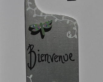 Hand painted plywood hanger for door decorated with embellishments and the word BIENVENUE