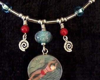 Swim Breaststroke: Sterling silver disk with swimmer in a pool.