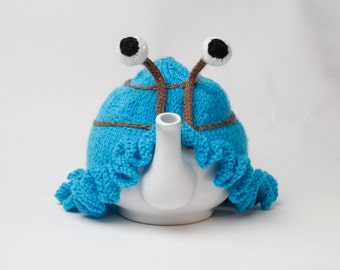Hand knitted blue snail tea cosy with frilly bottom and boggly eyes.  Fits 6 cup 1 litre pot.