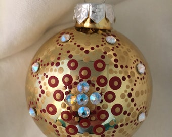 Gold Christmas Ornament dotted in Reds and gold acrylic and adorned with 13 Swarovski crystals.