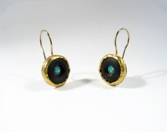 22 k solid  gold earrings , matte Onyx disk with center Opalite, solid gold wire and silver back. Will drag attention where ever you'll be.
