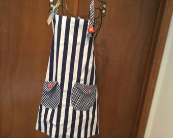 Reversible apron with contrating pockets and tulip buttons