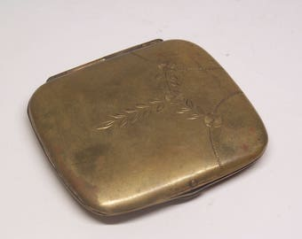 antique brass cigarette case with engraved floral pattern