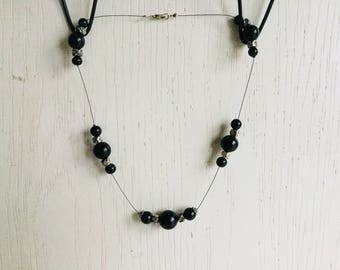 Floating necklace with black plastic beads