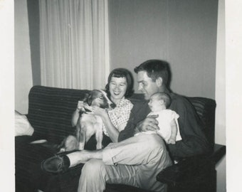 vintage photo 1960 Baby Squeals in Delight for Dog Between Mom and Dad on Couch snapshot
