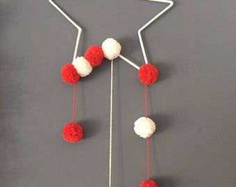 Star in knitting and its off white orange PomPoms