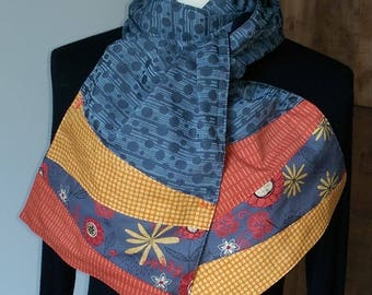 Thin grey fabric with yellow and orange etremites scarf.