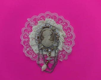large rosette has sew or paste made of lace cream Center with a cameo to decorate with bead is sew or paste
