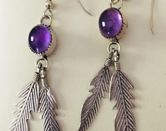 Sterling Silver with Amethyst cabochon stones above two engraved feathers
