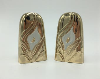 Gold colored tarnish resistant japanese lily salt and pepper shakers.