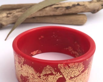 Handmade eco-resin wide bangle in cherry red with golden leaf detailing.