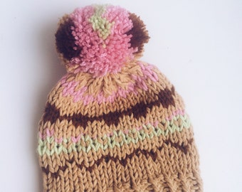 knitted hat with pattern and pompon.