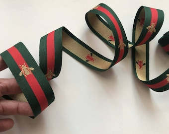 Ribbon green and red. Ribbon with gold bee.