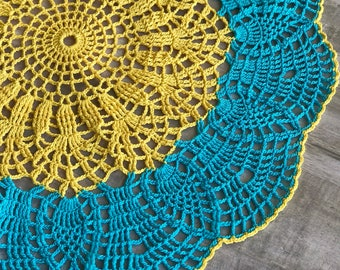 Round doily crocheted in a blue-yellow rainbow. Lace Table Mat. A gift for mom