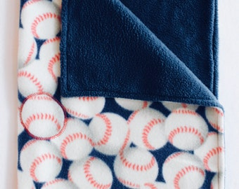 Sample--Discounted--Baseball and navy cozy fleece blanket. Edges sewn. Baseball image sewn in center to retain shape. Machine wash & dry