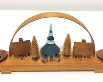 Vintage East German (GDR) candle holder, arch encasing a carved wooden village of a public building, houses, and trees.