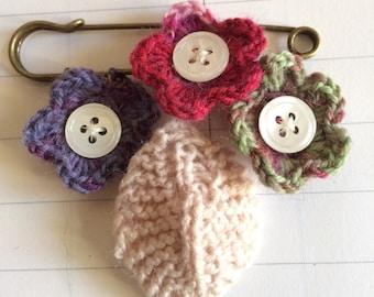 Crochet flower brooch on a kilt pin