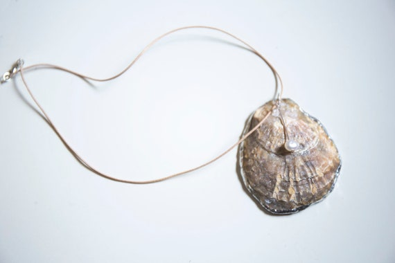 Soldered oyster shell with freshwater pearl on sand-coloured leather rope choker.