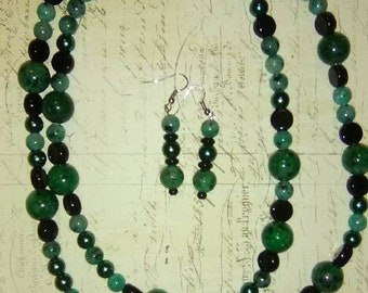 This is a hand made necklace and earring set made by me. It is a dual strand necklace with green chryscolla beads and black glass beads.