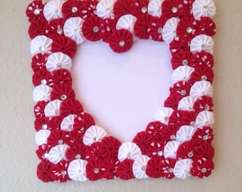 Frame with a heart shaped opening with red and white fabric yoyo's