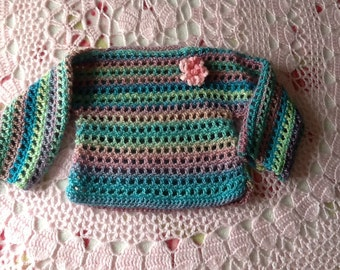 Crocheted slip-on, boat neck sweater in predominantly teal variegated yarn.  Trimmed with pink crocheted flower, for 24-36 months