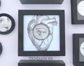 Frame heart curiosity with ceramic eye