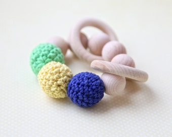 Teething toy with crochet wooden beads and 2 wooden rings. Blue, yellow, green wooden beads rattle.
