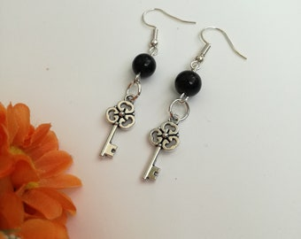 Pendant earrings with lucky charm in the shape of a key and black bead