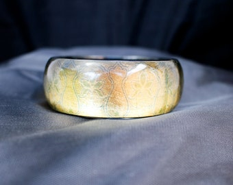 Gold floral design lucite cuff bangle. 1960s plastic jewellery.