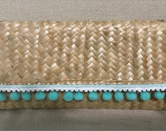 Straw clutch with aqua pom poms