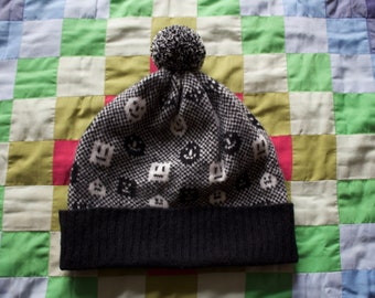 Monochrome geometric knitted 'Faces' design hat with pom-pom. Black and white lambswool hat.