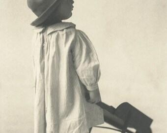 vintage photo 1910 Baby Boy From Back Smock Dress Hat Wheelbarrow Toy