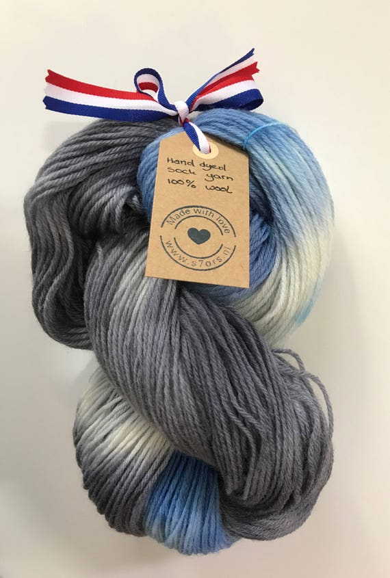 Hand dyed fine wool yarn in dark blue, grey and white.