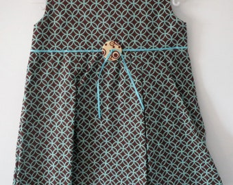 Girl, 18 months cotton pleated dress. Light turquoise design on brown background.
