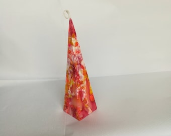 Pyramid candle with red, orange and white splashes to give a marbled effect