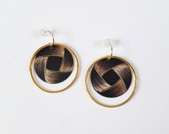 Round earrings etched brass with a decorative pattern reminiscent of a Ribbon.