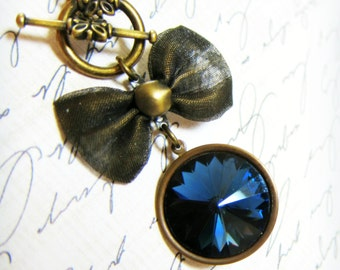Sapphire Moon- antiqued brass front closure bow necklace with a vintage round sapphire blue jewel pendant, montana blue