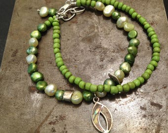 Green double strand Bracelet in pearls and glass beads.